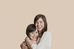 Portrait of young female friends hugging over colored background Stock Photo