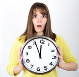 Portrait of a young female holding big clock against white backg Royalty Free Stock Photo