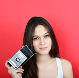 Portrait of young female holding vintage camera against red back Stock Photos