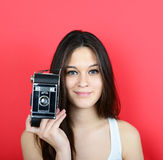 Portrait of young female holding vintage camera against red back Stock Photo