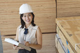 Portrait of young female industrial worker writing on clipboard with wooden planks in background Royalty Free Stock Photography