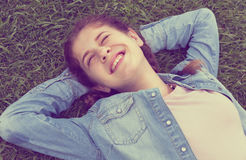 Portrait of  young female while lying in spring green garden Stock Image
