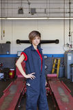 Portrait of a young female mechanic standing with hand on hip in car workshop Stock Photo