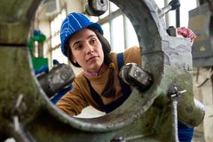 Female mechanic at factory. Portrait of young female mechanic wearing hardhat  looking into machine part while working at modern plant, copy space Royalty Free Stock Photography