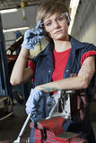 Portrait of a young female mechanic wearing protective eyewear in garage Stock Images