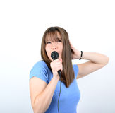 Portrait of a young female with microphone against white backgro Stock Image