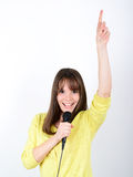 Portrait of a young female with microphone against white backgro Royalty Free Stock Image