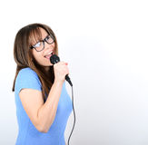 Portrait of a young female with microphone against white backgro Royalty Free Stock Photography