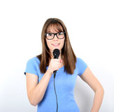 Portrait of a young female with microphone against white backgro Royalty Free Stock Images