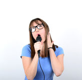 Portrait of a young female with microphone against white backgro Stock Photo