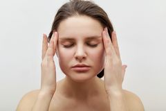 Horizontal headshot of young female model with closed eyes making herself facial massage. Portrait of young female model with closed eyes making herself facial royalty free stock photo