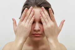 Portrait of young female model closing her eyes with her palms, making facial massage royalty free stock photos