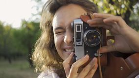 Portrait young female photographer with curly hair looking at the camera while taking photo using old camera in the. Attractive young photographer with curly stock video footage