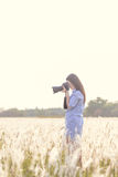 Portrait of the young Female photographer outdoors. In the grass field Stock Images