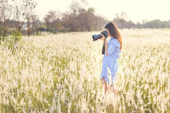 Portrait of the young Female photographer outdoors. In the grass field Stock Image