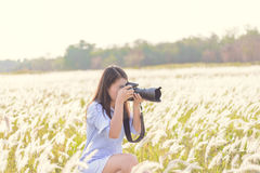 Portrait of the young Female photographer outdoors. In the grass field Stock Photography