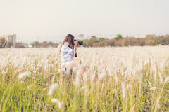 Portrait of the young Female photographer outdoors. In the grass field Royalty Free Stock Images