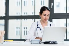 Portrait of young female physician working on laptop in the office. Portrait of young female physician wearing white medical gown while working on laptop in the Stock Images