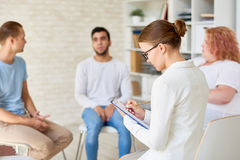 Young Female Psychologist Leading Therapy Session Stock Photo