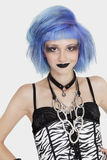Portrait of young female punk with dyed hair over gray background royalty free stock images