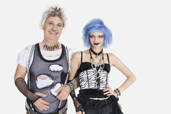 Portrait of young female punk standing arm in arm with senior man wearing ripped clothes over gray background royalty free stock image