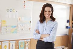 Portrait of young female school teacher in classroom stock image