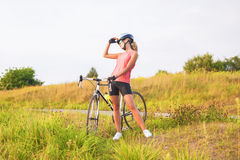 Portrait of a young female sport athlete with racing bike restin Royalty Free Stock Photo