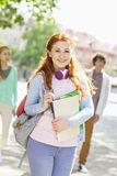 Portrait of young female student with friends in background on street Stock Photography