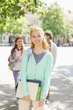 Portrait of young female student with friends in background on street Stock Images