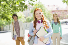 Portrait of young female student with friends in background on street Royalty Free Stock Image