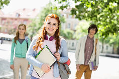 Portrait of young female student with friends in background on street Royalty Free Stock Images