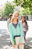 Portrait of young female student with friends in background on street Stock Image