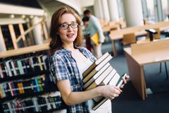 Portrait of young female student in library. Portrait of young female student in university library Stock Photo