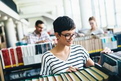 Portrait of young female student in library. Portrait of young female student in university library Royalty Free Stock Photo