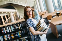 Portrait of young female student in library. Portrait of young female student in university library Royalty Free Stock Photography