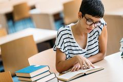 Portrait of young female student in library. Portrait of young female student in university library Stock Photography