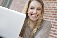Portrait of young female student using a laptop. Portrait of a smiling female student using a laptop Royalty Free Stock Photo