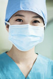Portrait of young female surgeon wearing surgical mask in the operating room, close- up Stock Images