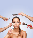 Portrait of young female surrounded by hands with beauty tools Royalty Free Stock Images