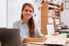 Portrait of young female teacher at desk looking to camera Stock Photo