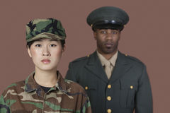 Portrait of young female US Marine Corps soldier with male officer in background royalty free stock photography