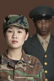 Portrait of young female US Marine Corps soldier with officer in the background royalty free stock photos