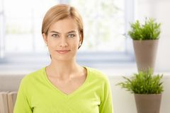 Portrait of young female in vivid green smiling Royalty Free Stock Image