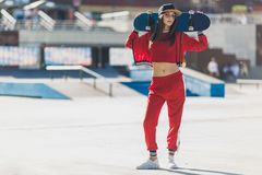 Portrait of young female wearing black hat, red clothing skateboarder holding her skateboard. Woman with skating board stock image