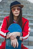 Portrait of young female wearing black hat, red clothing skateboarder holding her skateboard. Woman with skating board stock images