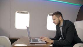 Portrait of young financial analyitc worling on laptop in private jet. lawyer or entrepreneur plane. Portrait of young financial analyitc worling on laptop in stock video footage