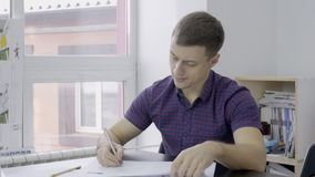 The portrait of young financial analytic who is checking the bitcoin exchange rates reports in his office. The portrait young financial analytic who is checking stock video footage