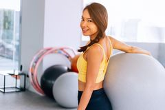 Portrait of young fit Asian woman holding exercise swiss ball and smiling at camera. Lively female fitness model image.  royalty free stock image