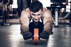 Young athlete excersises with barbell ab rollout. Portrait of young fit man on gym floor doing exercises with barbell ab rollout Stock Photography