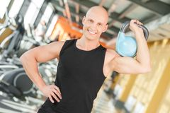 Portrait of young fit man lifting a kettlebell Stock Photos